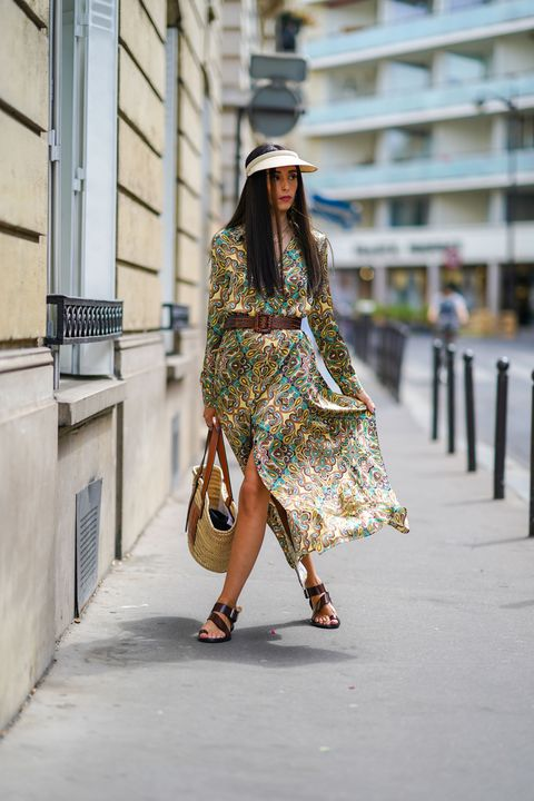 paris, france   july 15 gabriella berdugo wears a cap, a maison sarah lavoine green floral print silky flowing dress, a max mara large brown leather belt, black leather gladiator sandals, a loewe large summer basket straw bag with brown leather inserts, on july 15, 2020 in paris, france photo by edward berthelotgetty images
