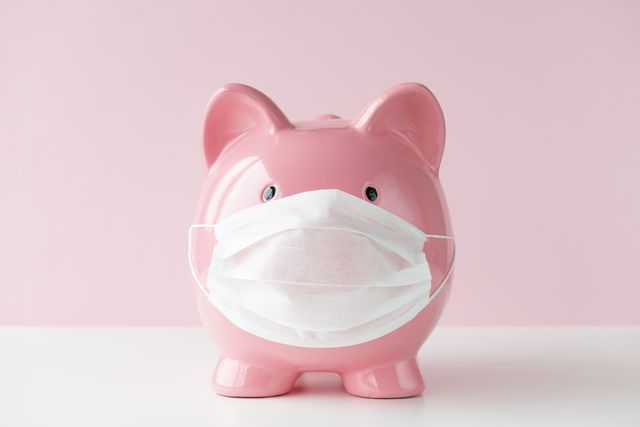 piggy bank with protective face mask on white table in front of a pink wall representing medical costs