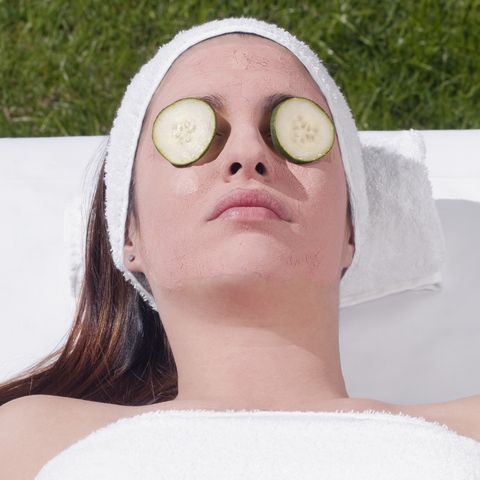Cucumber slices on a woman's eyes