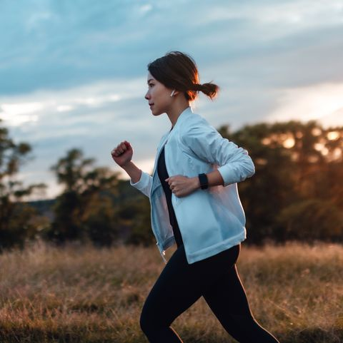 side view of determined young asian woman listening to music with earphones, jogging at the park, against sunset