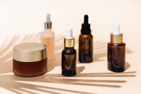 spa cosmetics in brown glass bottles on broun background copy space for text beauty blogger, salon therapy, branding mockup, minimalism concept various facial massage oils for spa treatment