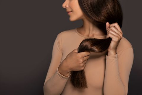 brunette girl with long straight and shiny hair beauty skin woman holding her strong and healthy hair in her hands over grey background cosmetic hair beauty salon concept