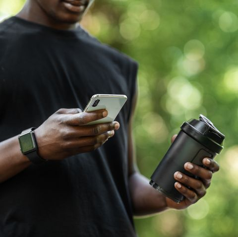 Fitness mobile application cropped of african athlete checking for sport app on cellphone during break, holding bottle with protein drink, blurred park background, copy space