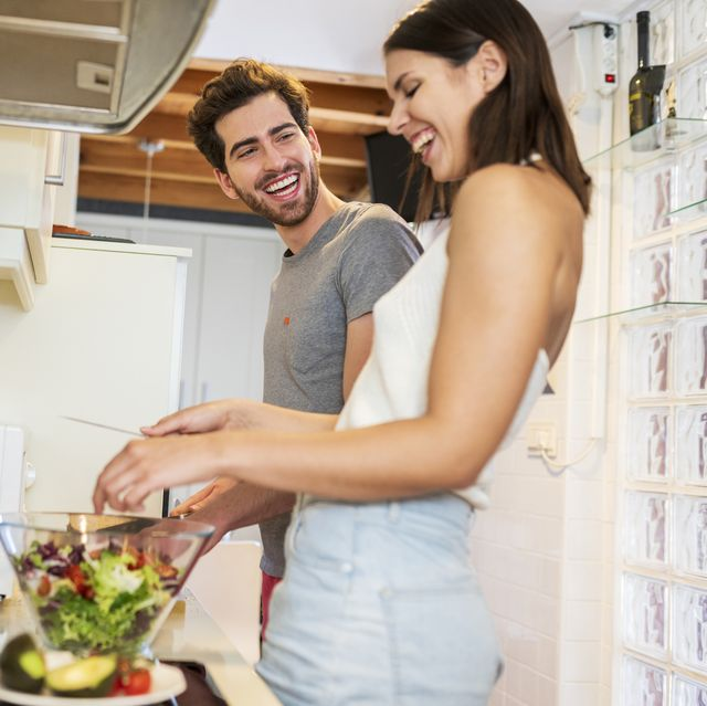 cheerful young couple preparing meal together in kitchen at home
