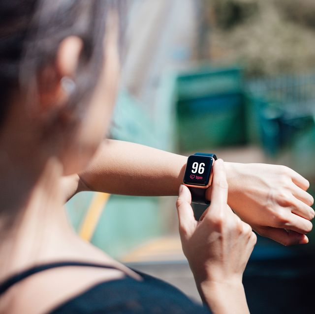 over the shoulder view of a young woman wearing smart watch, using fitness app to check her training progress