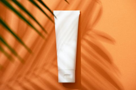 white plastic tube with face, hand and body cream on an orange background with palm leaves and shadow sun protection lotion, sunscreen summer skin care concept with spf flat lay mockup