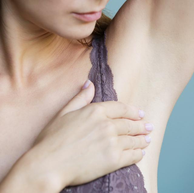 woman examining armpit area closely