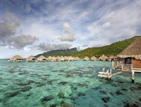 French Polynesia, Moorea Lagoon Resort, Bungalows over beautiful turquoise ocean.