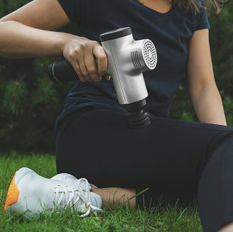 woman massaging leg with massage percussion device after workout