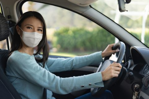 portrait of a latin american woman wearing a facemask while driving a car to avoid an infectious disease   pandemic lifestyle