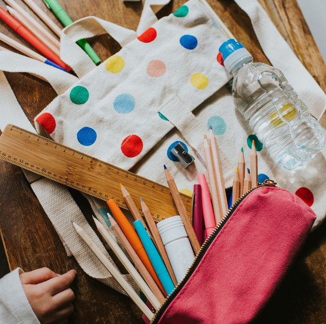 a childs little spotty canvas schoolbag on a sunny wooden table, with a pencil case filled with pens and colouring pencils, a ruler, pencil sharpener, a rubber and a glue stick surround focus is on a miniature plastic water bottle child stands off to the side looking at the spread