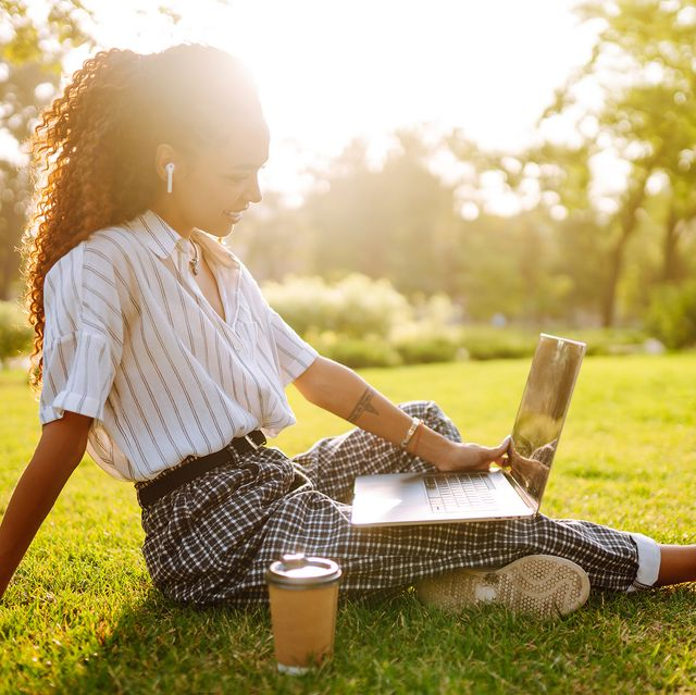 young woman sitting on green grass with laptop and coffeesmiling woman using laptop and wireless earphone for video call sunset light lifestyle concept