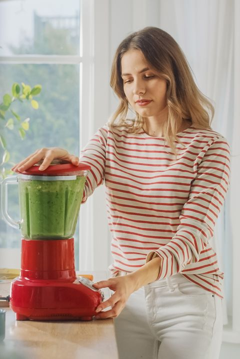 beautiful young female preparing a healthy green smoothie in a blender authentic stylish kitchen with healthy vegetables natural clean products from organic farming used to make drinks