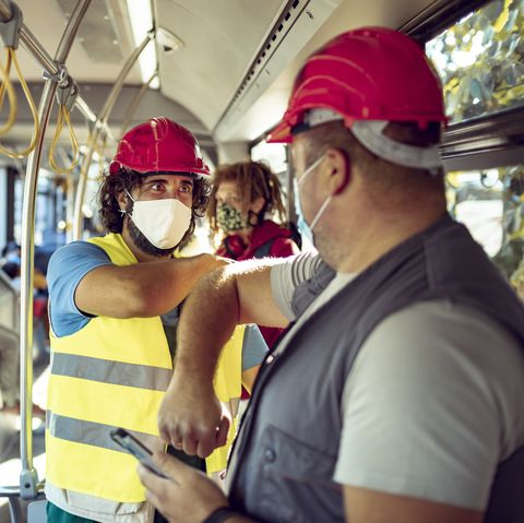 Close up of two construction workers wearing mask commuting to work on a bus