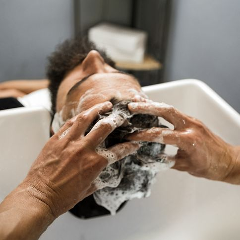 young man getting his hair washed by a male hairdresser