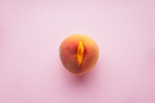 juicy peach on a pink background sex concept