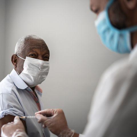nurse applying vaccine on patients arm