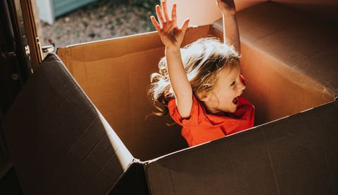 cute and joyful little girl excitedly leaps inside a huge cardboard box in sunlight she throws her hands up in excitement background image with child being in soft focus, and box provides a space for copy