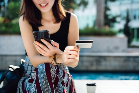 beautiful smiling young asian woman sitting in an urban park, enjoying coffee, shopping online with smartphone and making mobile payment with credit card on hand online shopping and mobile payment concept