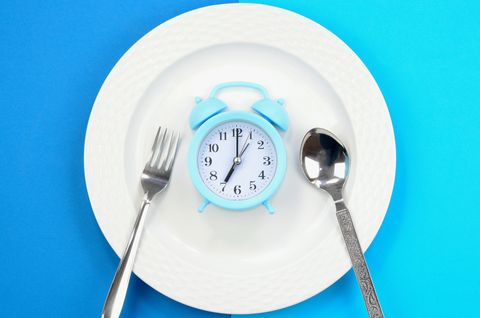 concept of diet and weight loss alarm clock on a white plate