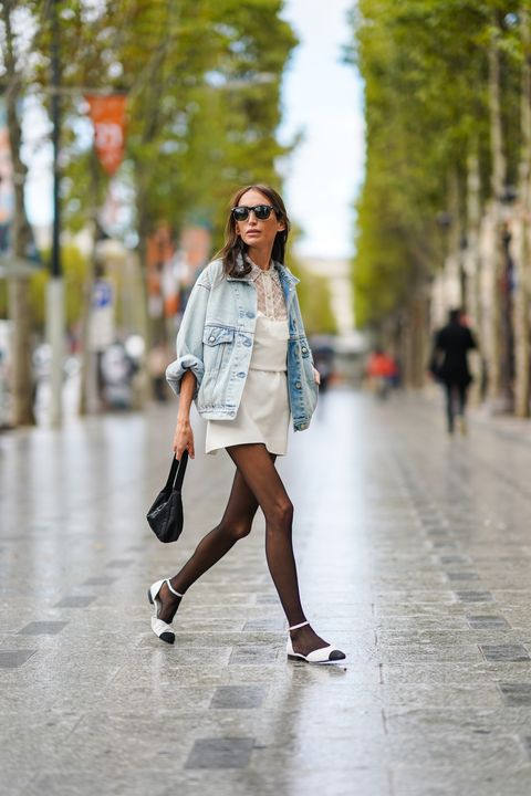 paris, france   october 06 a guest wears sunglasses, a pale blue denim jacket, a white dress with mesh and floral embroidery, black tights, a black prada bag, white pointy shoes, outside miu miu, during paris fashion week   womenswear spring summer 2021, on october 06, 2020 in paris, france photo by edward berthelotgetty images