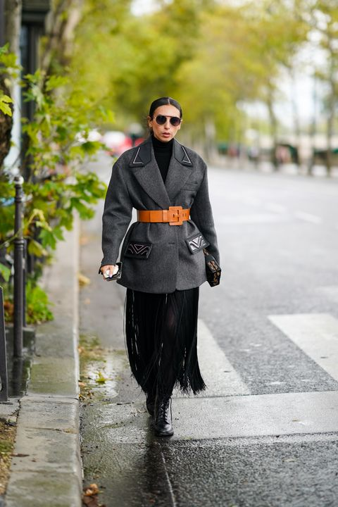 paris, france   october 06 gabriella berdugo wears sunglasses, a gray oversized prada coat, an orange large belt, a fringed skirt, black pants, leather boots, outside louis vuitton, during paris fashion week   womenswear spring summer 2021, on october 06, 2020 in paris, france photo by edward berthelotgetty images