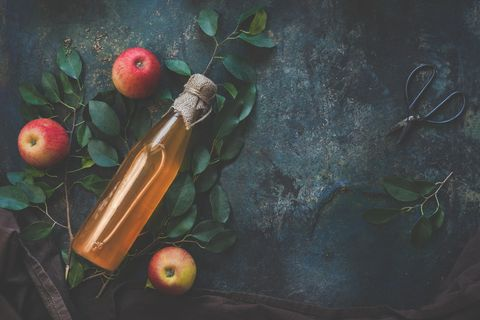 homemade apple cider vinegar on dark rustic background with apples, top view