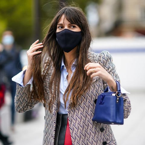 paris, france   october 06 a guest wears a black face mask, a vuitton bag, a coat with shoulder pads and printed geometric patterns, a pale blue shirt, outside louis vuitton, during paris fashion week   womenswear spring summer 2021, on october 06, 2020 in paris, france photo by edward berthelotgetty images