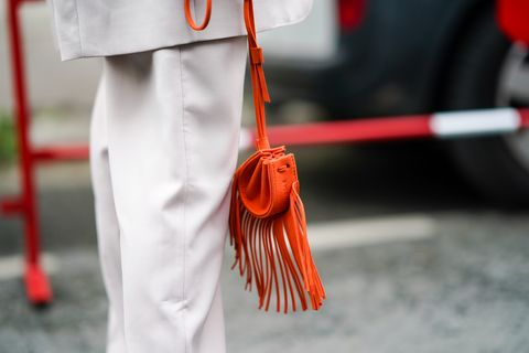 paris, france   september 30 a guest wears an orange bag with fringes, outside kenzo, during paris fashion week   womenswear spring summer 2021, on september 30, 2020 in paris, france photo by edward berthelotgetty images