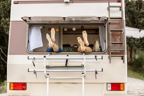 feet of a couple on a window of a campervan