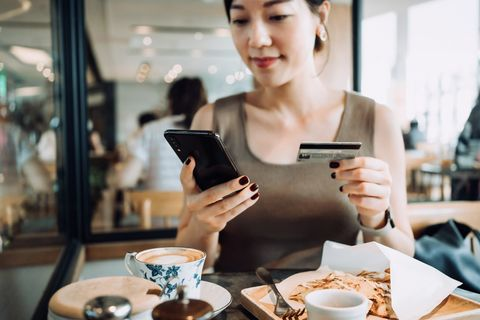 beautiful smiling young asian woman managing online banking with smartphone and making mobile payment with credit card on hand while having meal in a restaurant