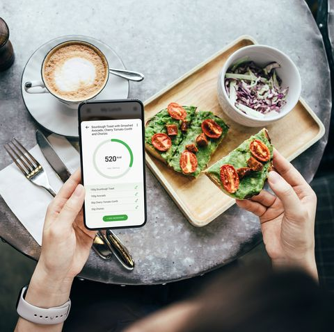 overhead view of young asian woman using fitness plan mobile app on smartphone to tailor make her daily diet meal plan, checking the nutrition facts and calories intake of her meal, sourdough toast with smashed avocado and cherry tomatoes in a restaurant