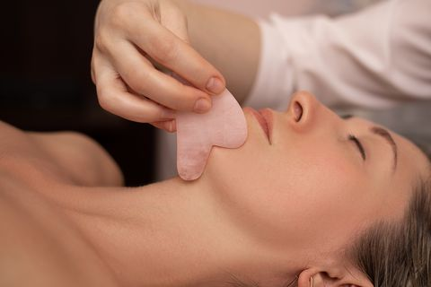 young and beautiful woman during chinese traditional massage   gua sha close up photo beauty treatment in spa salon anti aging skin care