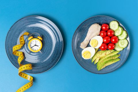plates with food and alarm clock on a blue background, intermittent fasting concept