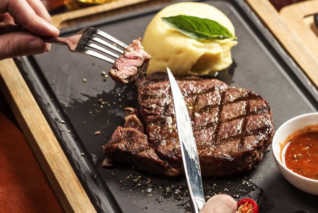 hands cutting up steak