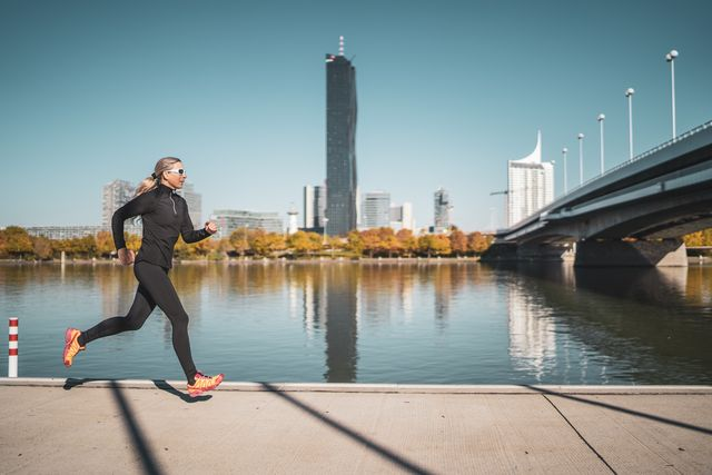 side view female mature adult athlete jogging alone along riverside in city on sunny day in autumn with urban skyline in background