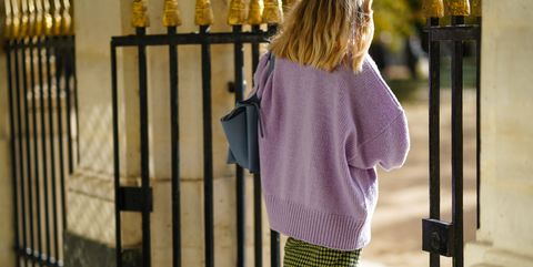 paris, france   october 26 a passerby wears a pale purple  mauve wool oversized pullover, a yellow and black skirt with printed patterns, a blue bag, on october 26, 2020 in paris, france photo by edward berthelotgetty images