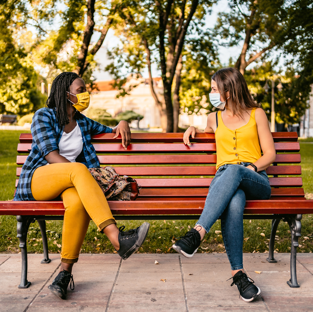 two friends in face masks sitting on opposite sides of bright red bench in park