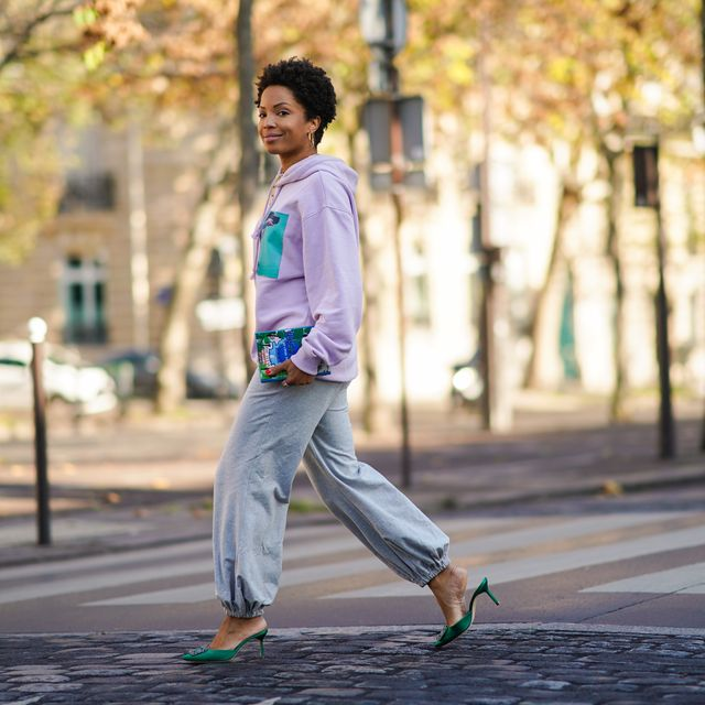 paris, france   november 05 ellie delphine wears a mauve pale purple hoodie sweater with a printed green patch depicting a hand and a dog from acne studios, gray sportswear pants from norma kamali, a book shaped bag in the spirit of miami beach from olympia le tan, green pointy bejeweled shoes from manolo blahnik, a golden chain necklace, earrings, on november 05, 2020 in paris, france photo by edward berthelotgetty images