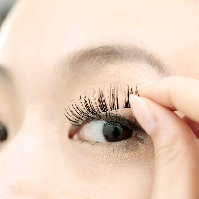 woman attaching false lash