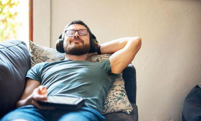man reclining on sofa wearing headphones