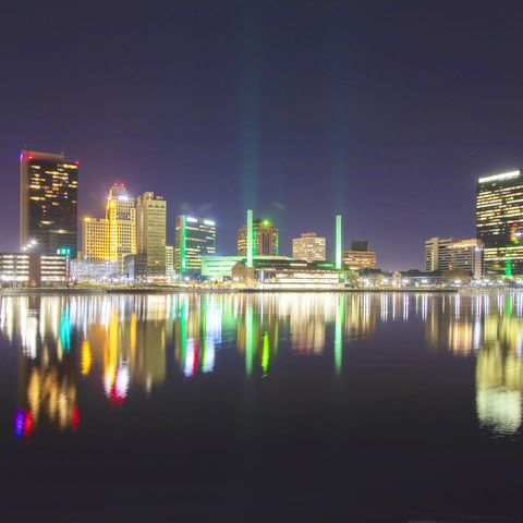 as seen in this image, toledo ohio has a colorful night presence the lights of the city are reflected on the calm surface of the maumee river, while some also project upward into the night sky