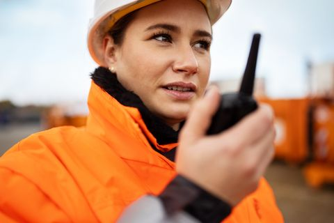 close up of a woman foreman talking over walkie talkie in plant warehouse worker reporting via walkie talkie