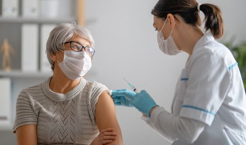 doctor giving a senior woman a vaccination virus protection covid 2019