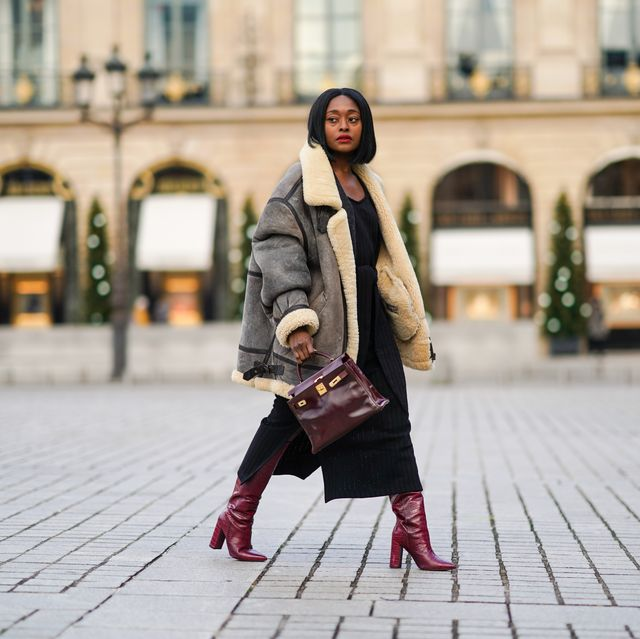 paris, france   december 06 fashion blogger linaose wears a bombardier aviator browngray jacket with sheep wool inner lining from acne studio, a black slit dress from sancia, a burgundy leather bag kelly hermes 28, purple leather crocodile pattern high heeled pointy boots from bianca di, on december 06, 2020 in paris, france photo by edward berthelotgetty images