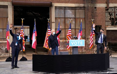 atlanta, ga   december 15 us president elect joe biden, c and us democratic senate candidates jon ossoff r and rev raphael warnock l wave to the crowd during a drive in rally at pullman yard on december 15, 2020 in atlanta, georgia biden's stop in georgia comes less than a month before the january 5 runoff election for ossoff and warnock as they try to unseat republican incumbents sen david perdue and sen kelly loeffler photo by drew angerergetty images