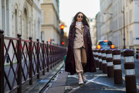 paris, france   december 15 gabriella berdugo wears  sunglasses, a white turtleneck pullover, earrings, a necklace, a bi color beige and brown oversized blazer jacket and suit pants from salisa nyc, beige nude biker platform shiny boots from agl, a leather vynil aubergine colored  purple trench coat from maison natan, a green quilted leather chanel bag, on december 15, 2020 in paris, france photo by edward berthelotgetty images