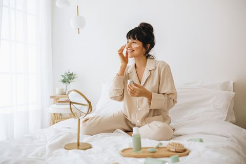 happy woman doing routine skin care at home with beauty products woman sitting on bed at home and applying face cream