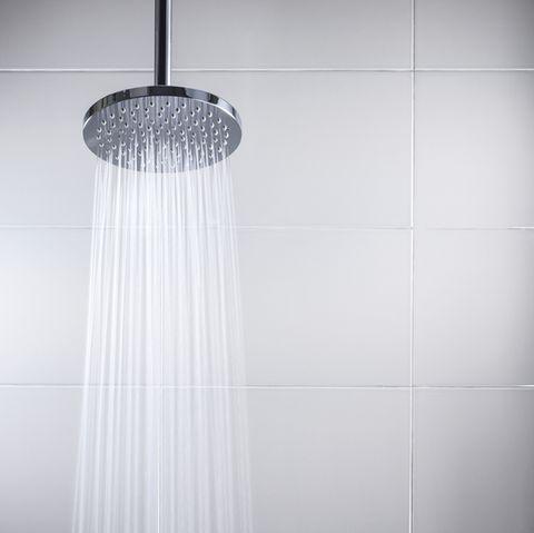 water running from modern rain shower head in tile shower