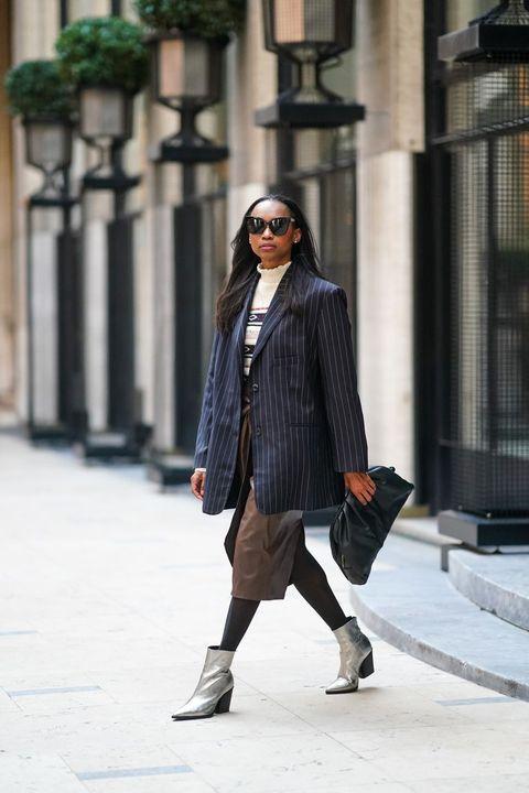 Παρίσι, Γαλλία 09 Ιανουαρίου emilie joseph φοράει γυαλιά ηλίου, ένα σκούρο μπλε ριγέ μπλουζάκι σακάκι από το κατάστημα frankie, ένα λευκό μάλλινο πουλόβερ με τυπωμένες ρίγες και γεωμετρικά σχέδια από την isabel marant, μια καφέ δερμάτινη φούστα από το zara, μαύρο καλσόν, ένα μαύρο δέρμα τσάντα από μάνγκο, ασημένια μποτάκια από τον jonak, στις 09 Ιανουαρίου 2021 στο Παρίσι, φωτογραφία της Γαλλίας από τον edward berthelotgetty images